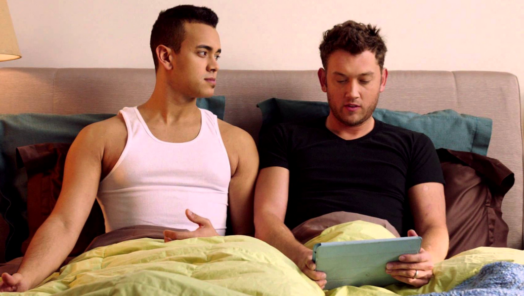 young gay couple sitting upright in bed looking at iPad or tablet