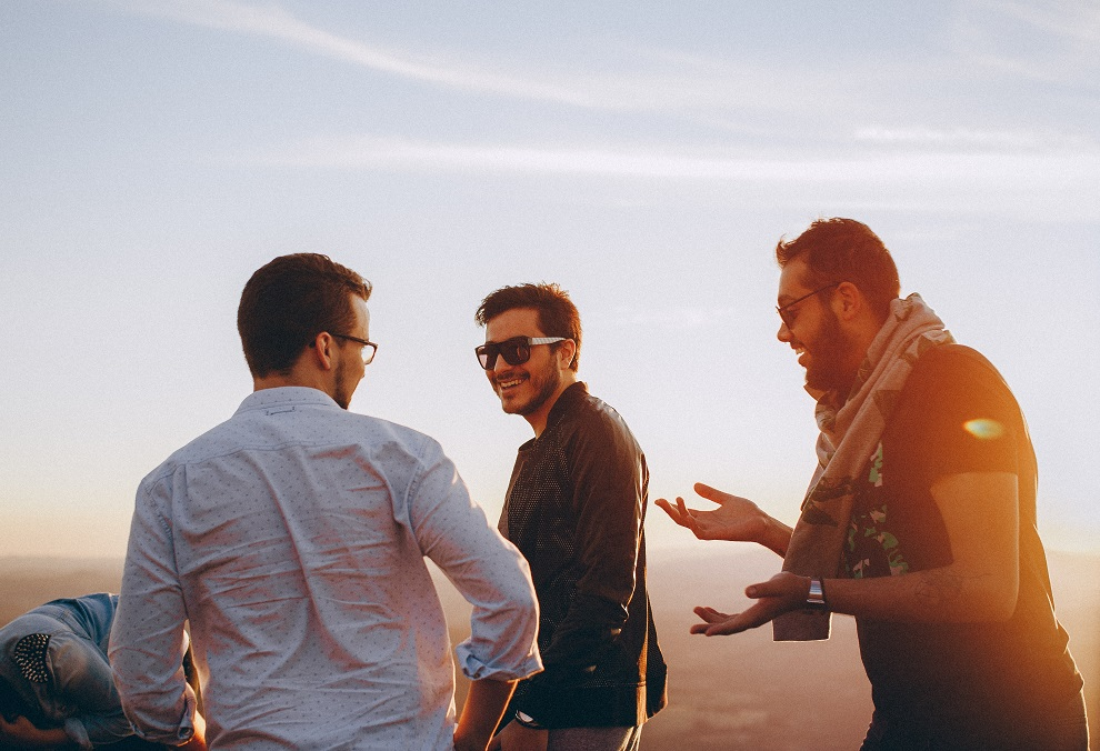 three male adults having fun at the beach with back-lit sunset