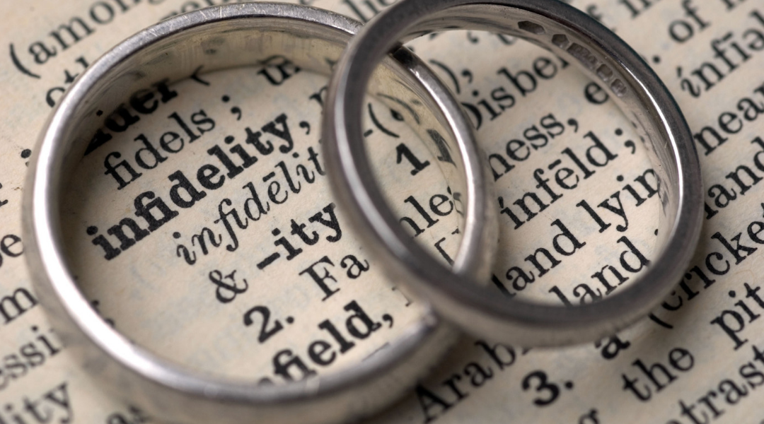 "Two silver rings overlapping on top of dictionary entry on ""infidelity"""
