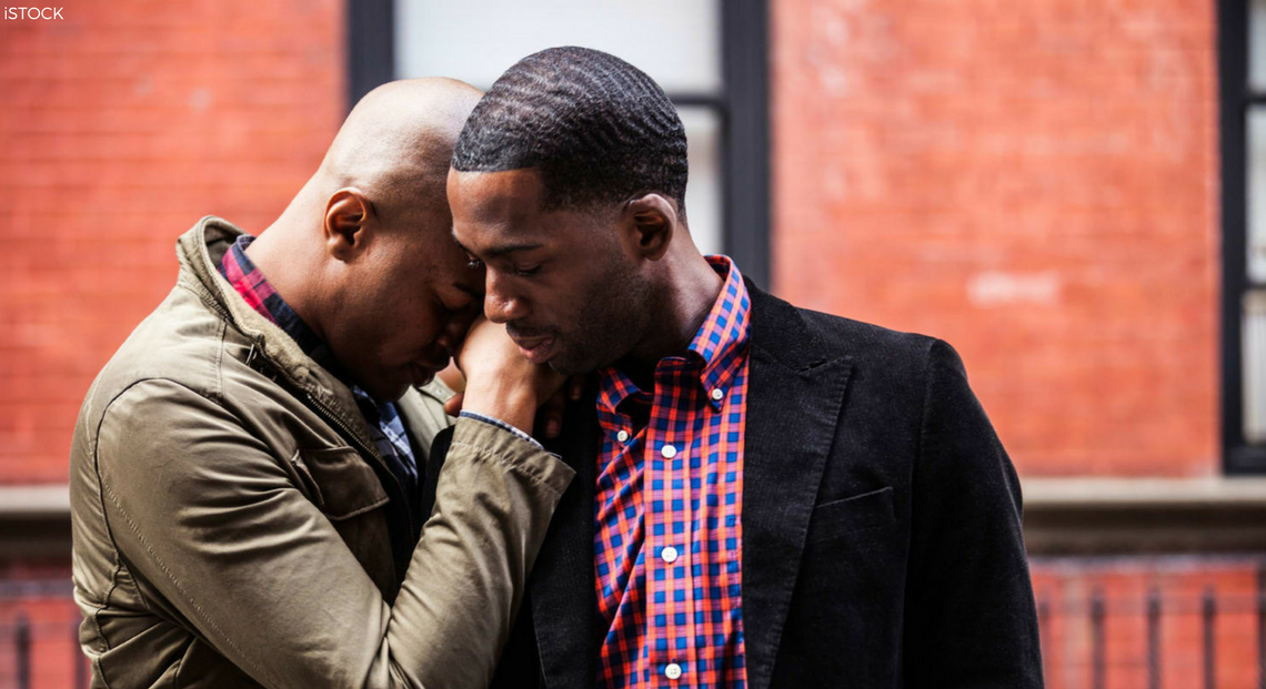 Black gay couple with one partner laying head and hand on shoulder of other partner