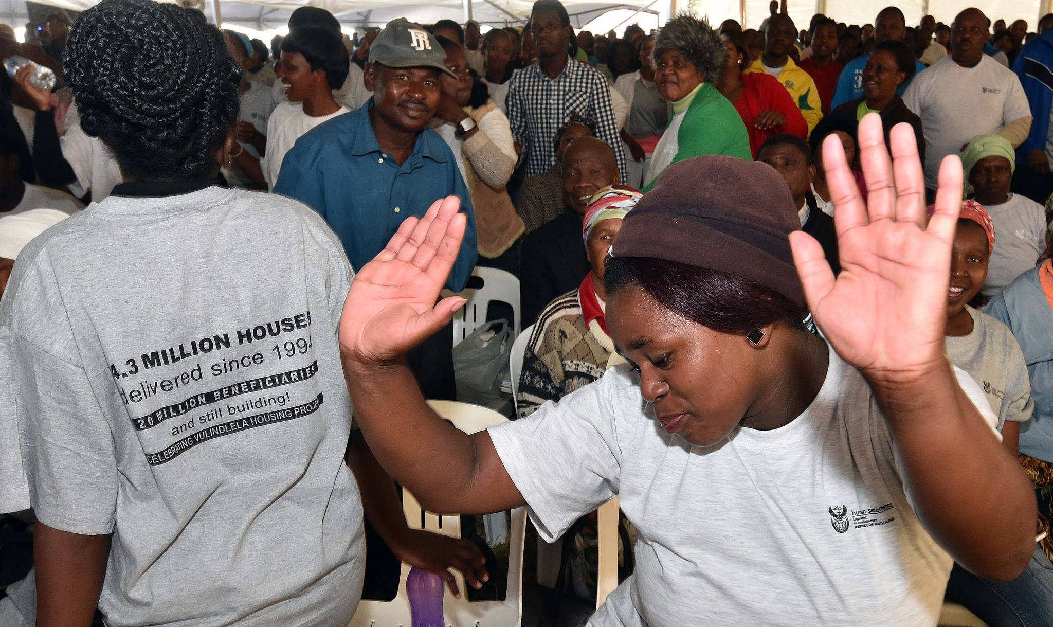 South African woman with hands in the air dancing at community event