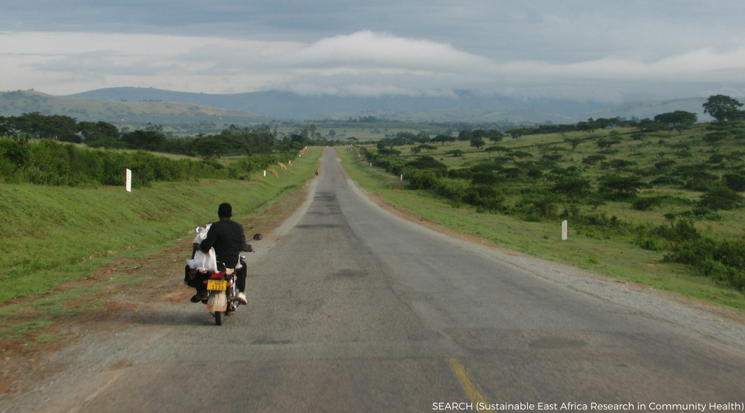 Sub-Saharan local riding a motorbike on an open road