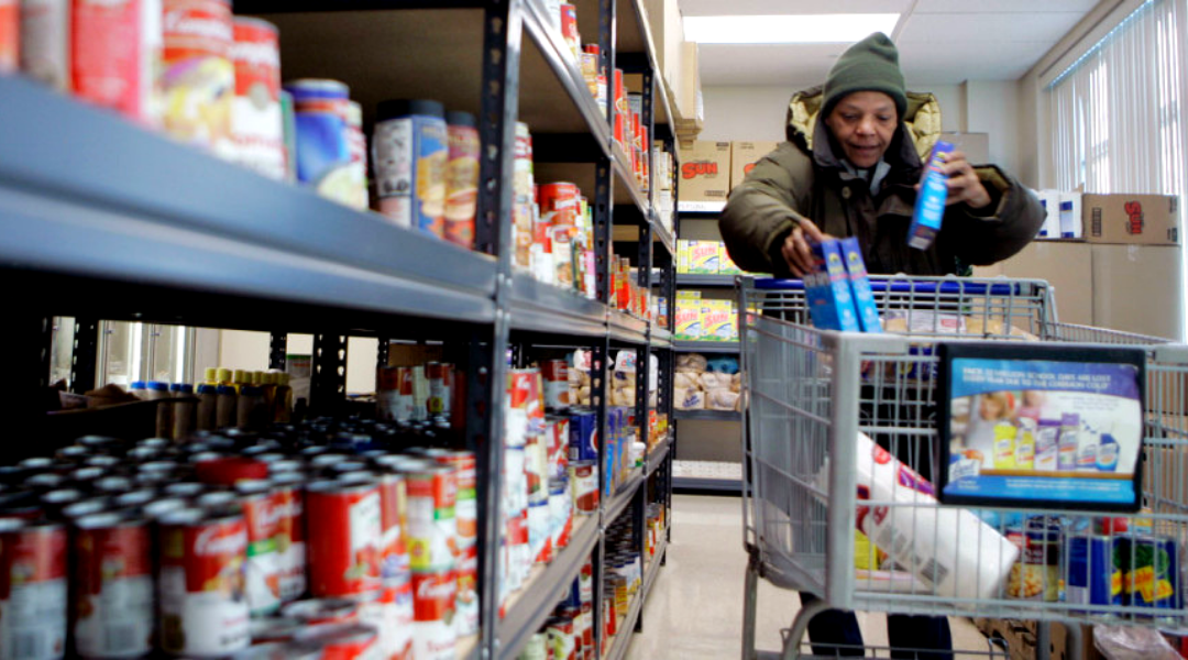 Black woman pushing a cart with food items in a grocery store