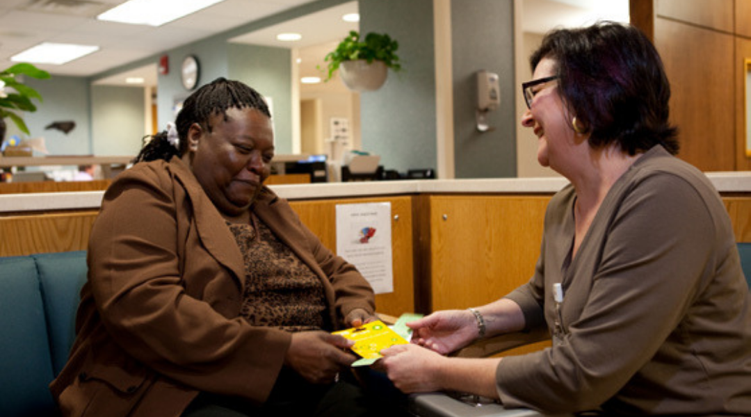 Patient living with HIV smiling with smiling primary care provider
