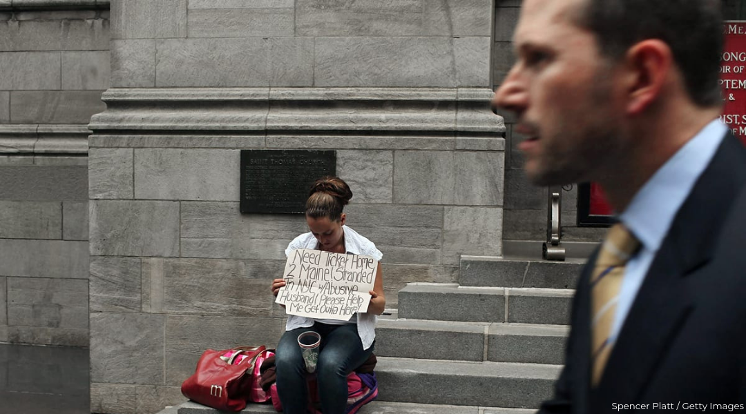 Woman sitting on stone steps and holding up sign asking for money to travel and white businessman passing by