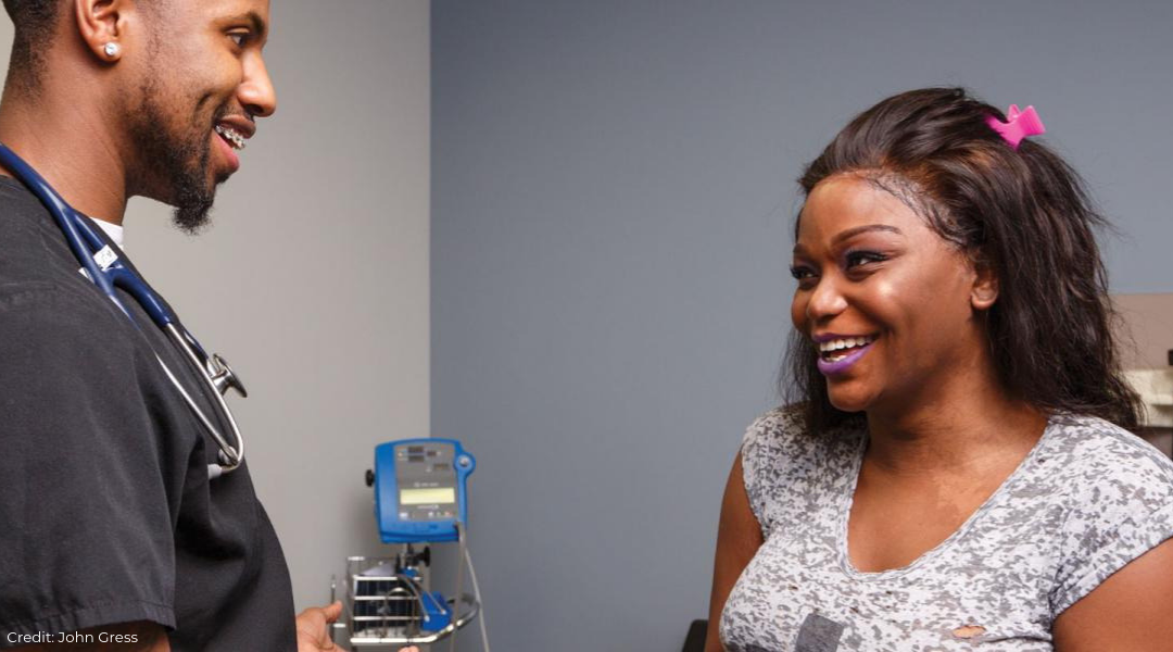 Black male healthcare provider with black transgender woman patient, both smiling