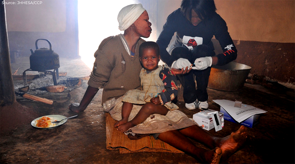African mother with her infant child being tested for HIV by healthcare outreach worker