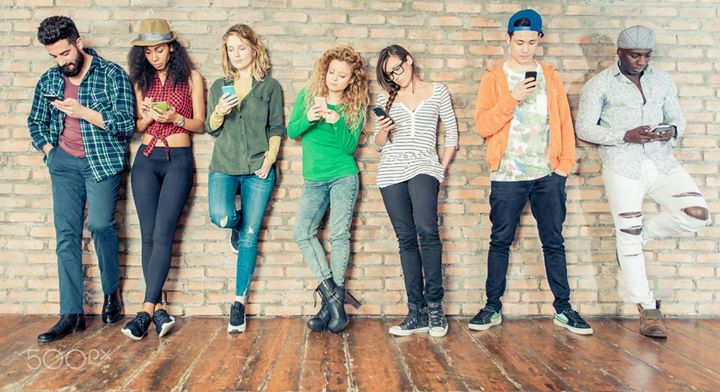 Nine young adults leaning against a wall checking their smart phones.