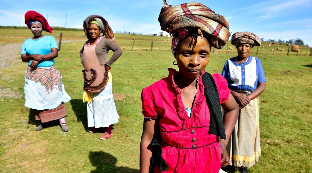 Four South African women standing in a grassy field.