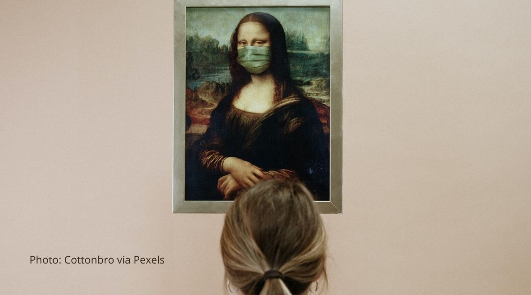 A woman studies a painting of the mona lisa who is wearing a protective mask