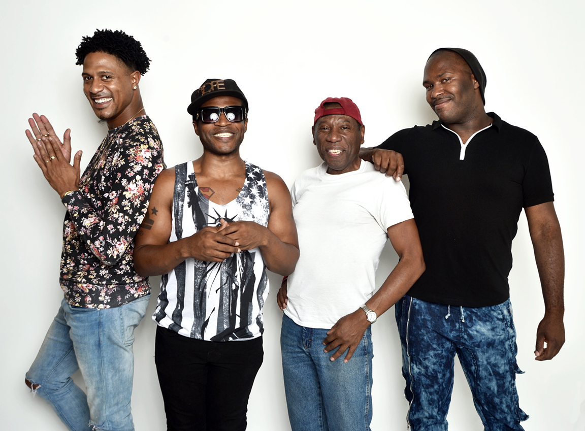 Four cheerful gay Black men posing for a photoshoot
